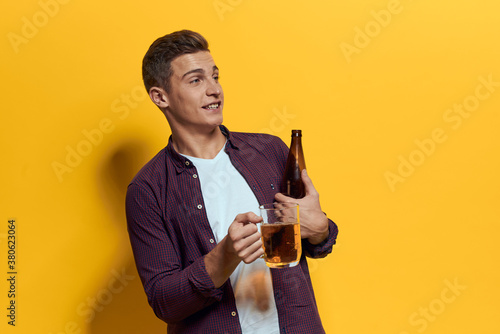 Tablou Canvas cheerful man mug of beer with bottle fun drunken lifestyle alcoholic yellow back