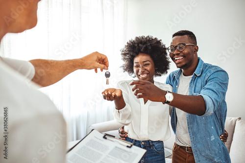 Fototapeta Real estate agent giving keys to couple of customers