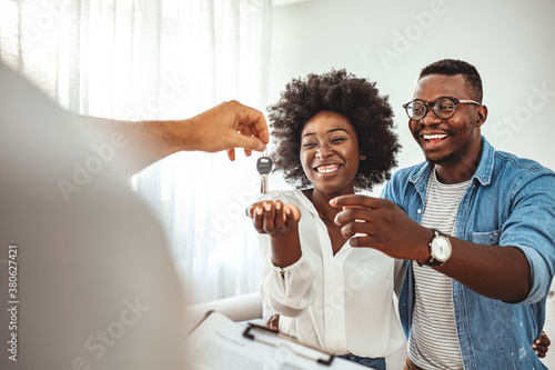 Fototapeta Couple Getting Keys From Realtor Of Their New Home. Portrait of financial adviser congratulating to a young couple for buying a new house. African-American  family buy new house obraz