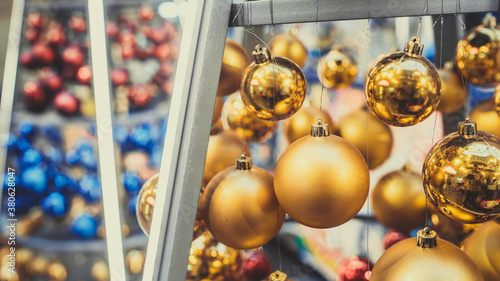 Fototapeta Close up of christmas toys suspended on metal construction in hall in shopping center. Yellow christmas balls hanging on strings for room decoration and create festive mood. obraz