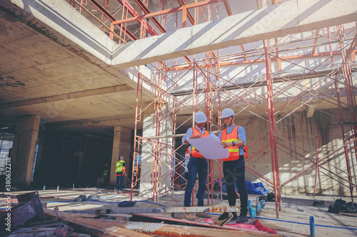 Fototapeta Structural engineer and foreman worker with touch pad discuss, plan working for building construction site. obraz