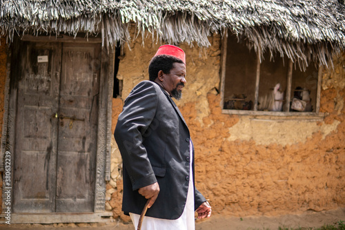Fotomural An African Older Man in Red Muslim Taqiyyah Fez Hat And Blazer on white Dress Mo