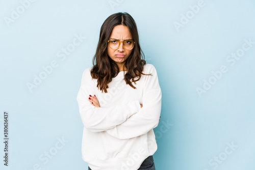 Photo Young mixed race hispanic woman isolated frowning face in displeasure, keeps arms folded
