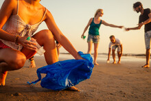 Focus On Cheerful Girl Cleaning The Sandy Beach From Garbage With Her Friends On Background Volunteer Team On Eco-friendly Movement In Goa India