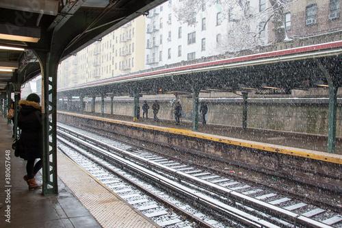 gros flocons de neige tombant sur les rails d'un gare avec des passagers attenda Canvas Print