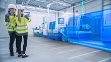 Two Engineers Use Digital Tablet Computer With Augmented Reality Software To Create 3D CNC Machinery, Equipment Visualization In Factory. Industry 4.0 Facility. Augmented Reality Graphics VFX Effects
