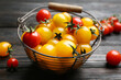Ripe red and yellow tomatoes in metal basket on dark wooden table, closeup