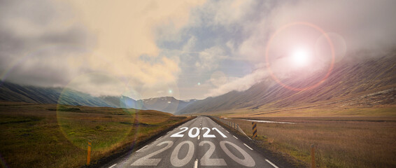 The word 2021 written on highway road in the middle of empty asphalt road at golden sunset and beautiful blue sky. High-quality photo
