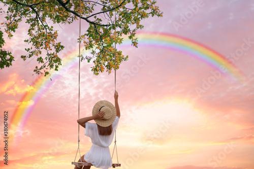 Fototapeta Dream world. Young woman swinging, rainbow in sunset sky on background obraz