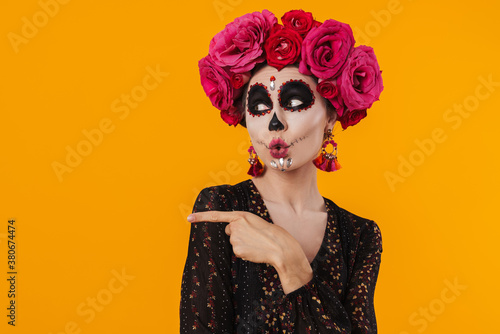Photo Photo of amusing girl in halloween makeup pointing fingers aside