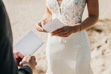 Close Up Of Bride And Groom Reading Wedding Vows From Paper At Wedding Ceremony In Nature