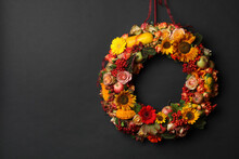 Beautiful Autumnal Wreath With Flowers, Berries And Fruits Hanging On Black Background. Space For Text