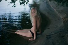 Blonde In Long Hair Sits Tople...