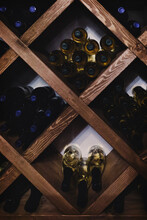 A Collection Of Wine Bottles In Dark Basement