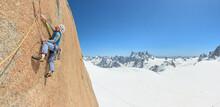 Man Rock Climbing On Steep Gra...
