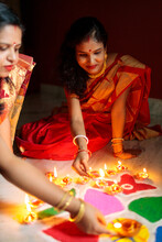 Indian Women Lighting Oil Lamps During Diwali And Decorating With Rangoli