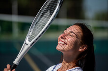 Beautiful Smiling Woman With A Shadow From A Tennis Racket On Her Face On A Sunny Day