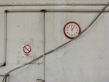 Wall With A Clock And A Non-smoking Poster.