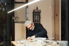 Senior Craftsman Making Electric Lamp