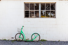 Green Amish Pedal Less Bicycle Leaned Against A Painted Brick Wall