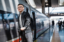 Businessman Waiting For Train At Train Station