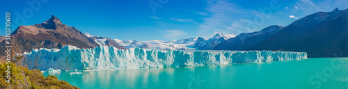 Photo Panoramic view over gigantic Perito Moreno glacier in Patagonia with blue sky and turquoise water glacial lagoon, South America, Argentina, at sunny day
