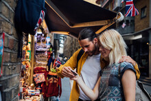 Young Couple Of Tourists Looking At Souvenirs On A Stall