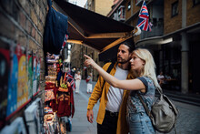 Young Couple Of Tourists Looking At A Souvenir Stall In London