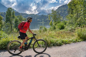 nice senior woman riding her electric mountain bike above the Freiberg Lake and a big ski flying hill in the Allgau Alps near Oberstdorf, Bavaria, Germany