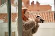 mujer de cabello naranja en exteriores haciendo una fotografía con cámara profesional y un abrigo de pelos gris