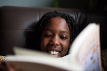Smiling Black Girl Reading A B...