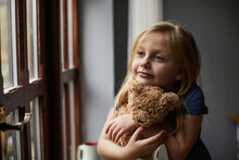 Child Hugging A Teddy Bear