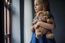 Child Holding A Teddy Bear