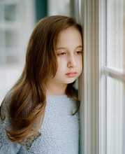 Young Girl Looking Sad And Bored Looking Out A Window