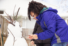 Teenager Creating And Building A Unique Snowman Outdoors On A Cold Winter Day