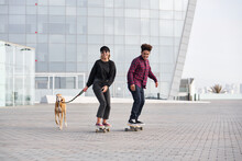 Diverse Couple With Dog Riding Skateboards In City