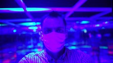 Portrait Of A Man In A Medical Mask In A Multi-colored Glowing Endless Space. Optical Illusions Can Use Color, Light And Patterns To Create Images That Can Be Deceptive Or Misleading To Our Brains.