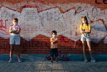 Kids Posing Besides A Brick Wa...