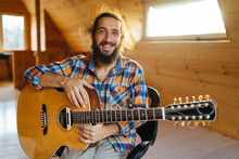 Portrait Of A Smiling Bearded Man With A Guitar