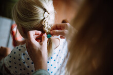 Mother Braiding Hair Of Her Li...