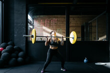 Woman Exercising With Barbells...
