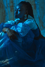Photo Of A Black Girl Sitting In A Fashionable Outfit And Golden Earrings In The Blue Light At The Studio