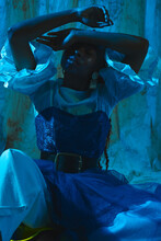 Photo Of A Black Girl Sitting In A Fashionable Outfit And Yellow Shoes In The Blue Light At The Studio Covering Her Face With Hands