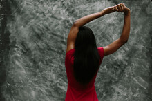 Woman In Red Stretching Her Arms Over Grey Background.