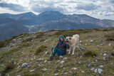 a woman and a big guard dog enjoy a moment on top of a mountain.