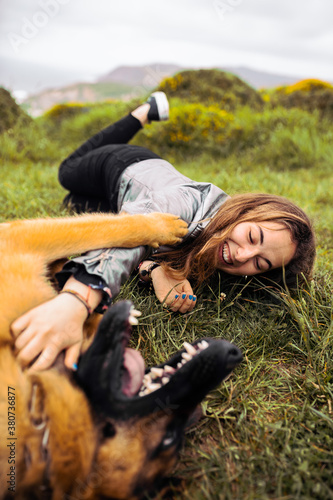 Laughing woman with dog on green meadow in hills - 380736877