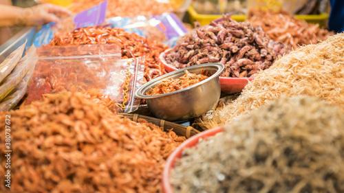 A stall vendor selling dry shrimp fish and various ingredients in popular market Fotobehang