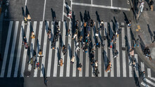 Elevated View Over Crowd Pedestrian Crossing In Road Intersection At Day