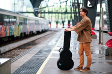 Side View Of Male Guitarist Standing With Musical Instrument In Case On Railway Station And Waiting For Train While Looking Away