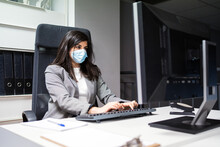 Confident Young Female Specialist In Formal Suit And Protective Mask Sitting At Desk And Using Computer While Working In Modern Workspace